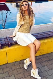 Portrait de mode en plein air de beau modèle, vêtu d'une tenue élégante et chaleureuse avec un manteau et des baskets, des cheveux blonds bouclés élégants, assis au club de yacht de la ville. style de rue d'automne.