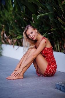 Portrait de mode en plein air beauté naturelle jeune jolie femme avec léger maquillage, boucles d'oreilles étoiles, bracelet et bague. femme en robe de fleurs d'été rouge