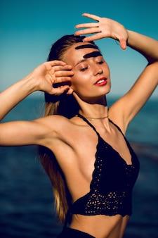 Portrait de mode en plein air d'une femme parfaite bronzée en élégant maillot de bain tricoté noir posant sur la plage.