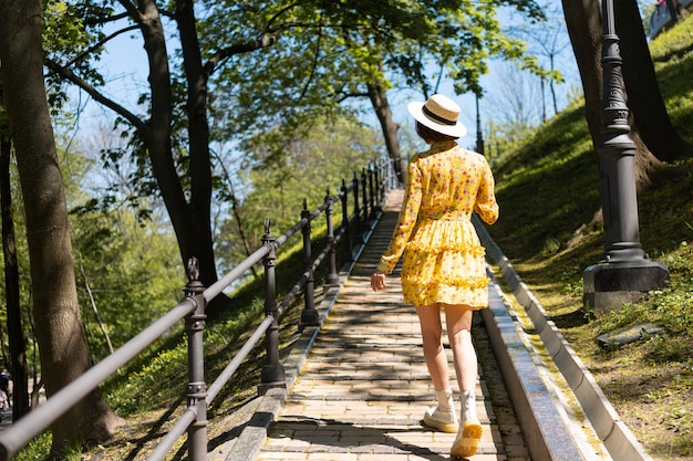 Portrait de mode en plein air de femme en robe d'été jaune et chapeau marchant sur le chemin dans le parc vue arrière