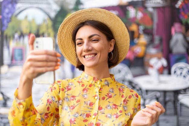 Portrait de mode en plein air de femme en robe d'été jaune sur le mur coloré de la rue