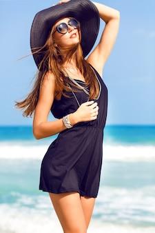 Portrait de mode en plein air de jeune femme heureuse assez souriante, s'amusant sur la plage, portant un chapeau et des lunettes de soleil élégant boho poussin, humeur positive