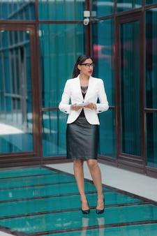 Portrait de mode pleine longueur de femme afro d'affaires sur le centre d'affaires