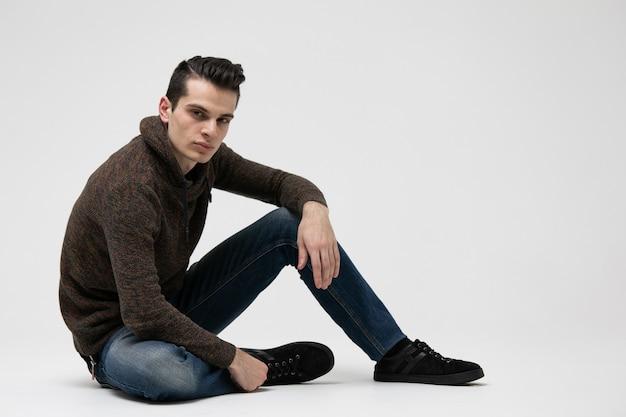 Portrait de mode studio de séduisant jeune homme à capuche marron et un jean bleu.