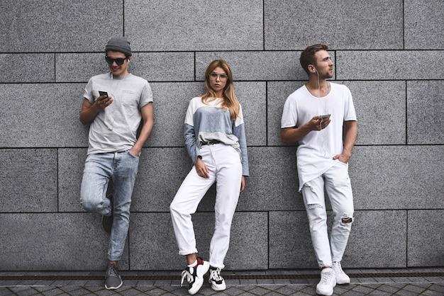 Portrait de mode de trois meilleurs amis posant dans la rue, vêtus d'une tenue élégante et d'un jean contre un mur gris.