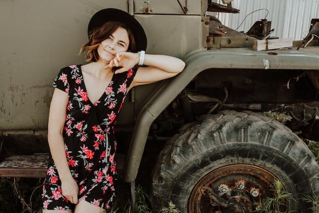 Portrait de mode de vie atmosphérique en plein air de la belle jeune femme aux cheveux noirs dans une robe noire dans un imprimé floral sur fond d'une vieille voiture de camion.