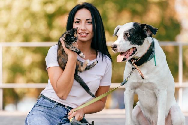 Portrait de mode de vie de la belle jeune fille brune avec petit chat et gros chien assis en plein air dans le parc. heureux adolescent souriant joyeux étreignant de beaux animaux de compagnie.
