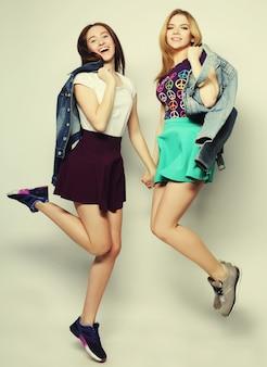 Portrait de mode de vie de deux jeunes filles hipster meilleurs amis sauter sur fond gris