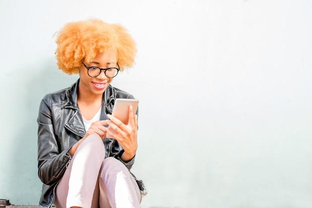 Portrait de mode de vie d'une femme africaine en veste de cuir assise avec téléphone sur fond de mur vert
