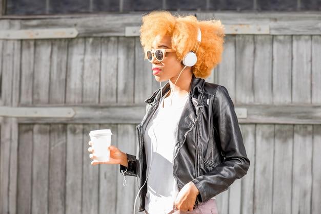 Portrait de mode de vie d'une femme africaine en veste de cuir debout avec une tasse de café à l'extérieur sur le fond du mur en bois