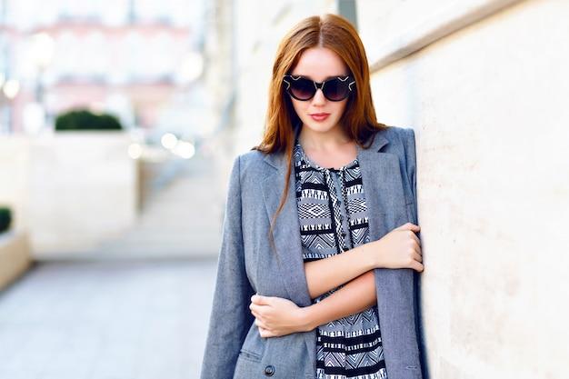 Portrait de mode de vie de femme, vêtue d'une élégante robe veste glamour et lunettes de soleil vintage, couleurs chaudes toniques, humeur positive.