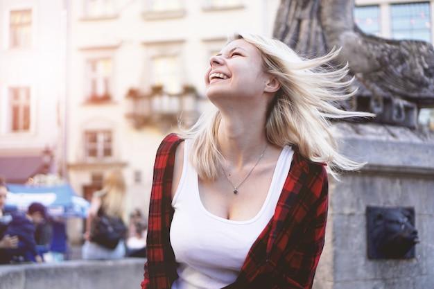Portrait de mode de vie d'une fille blonde heureuse à la mode portant une chemise rouge rock, un t-shirt blanc s'amusant à l'extérieur de la ville