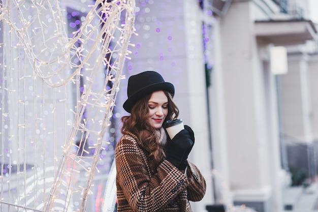 Portrait de mode de vie d'une fille magnifique. porter un manteau élégant et boire du café en ville