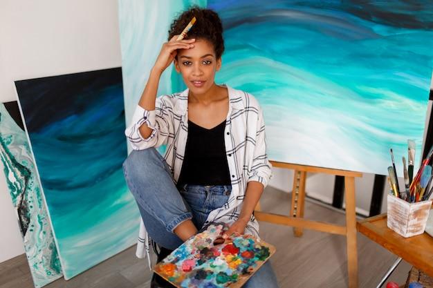 Portrait de mode de vie de jeune étudiant africain assis avec des illustrations dessinées à la main en acrylique abstrait mer au studio.