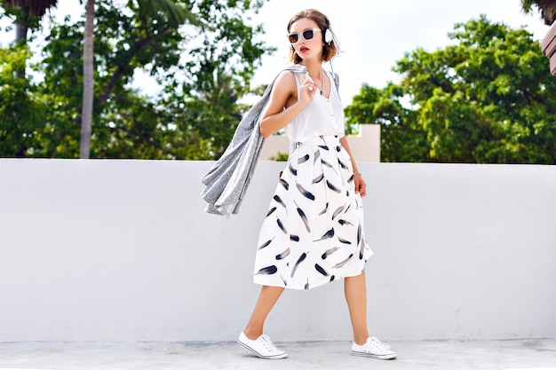 Portrait de mode de vie de jeune femme jolie heureuse sautant et s'amusant dans la rue à la belle journée d'été ensoleillée, écoutant la musique préférée aux écouteurs, tenue vintage élégante, couleurs fraîches et lumineuses.