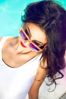 Portrait de mode de vie en plein air de jolie femme avec des lunettes de soleil