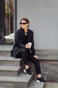 Portrait De Mode De Vie En Plein Air D'une Superbe Fille Brune. Boire Du Café Et Marcher Dans La Rue De La Ville. Photo gratuit