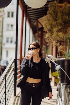 Portrait de mode de vie en plein air d'une superbe fille brune. boire du café et marcher dans la rue de la ville.