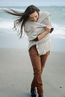 Portrait de mode de vie printanière d'une jeune femme élégante marchant sur une plage de la mer, vêtue d'une jolie tenue décontractée, profitant des week-ends et des voyages