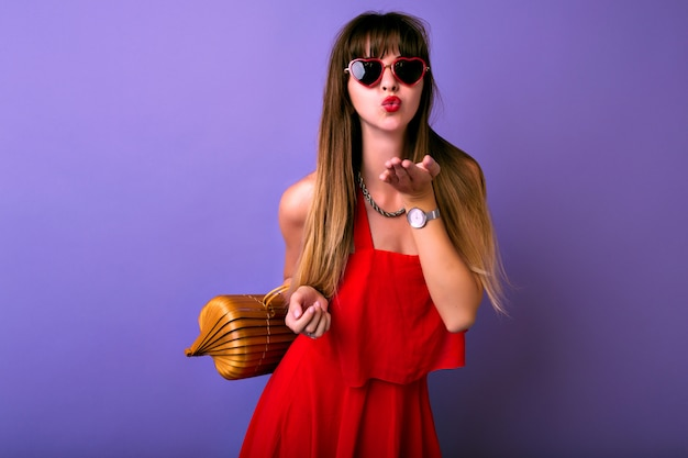 Portrait de mode de vie en studio de jolie femme brune à la mode vêtue d'une élégante robe rouge d'été, lunettes de soleil herat, sac en bois, envoi de baiser d'air.
