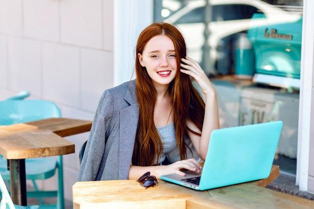 Portrait de mode ville en plein air de jeune femme d'affaires travaillant au café sur la terrasse en journée ensoleillée, tenue élégante décontractée, détails de menthe, à l'aide de son ordinateur portable, pause café, concept d'entreprise.
