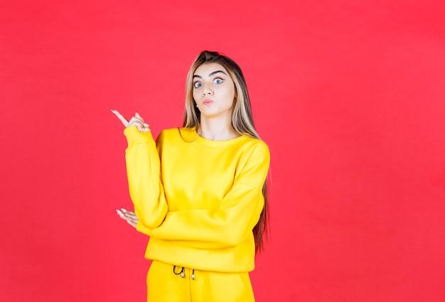 Portrait de modèle de belle femme debout et pointant vers le haut avec le doigt