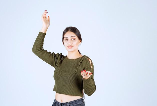 Portrait d'un modèle de belle jeune femme debout et posant sur un mur blanc.
