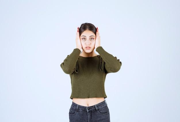 Portrait d'un modèle de belle jeune femme debout et tenant sa tête.