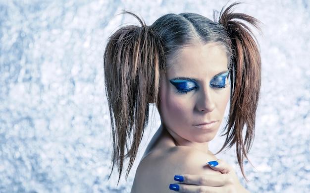 Portrait d'un modèle de belle jeune fille avec des nattes, un maquillage fantaisie brillant et une manucure bleue sur un fond métallique flou