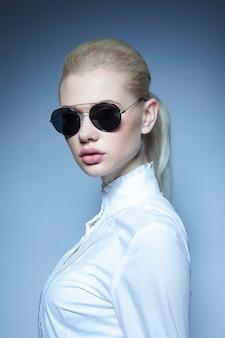 Portrait d'un modèle féminin blonde avec queue de cheval et lunettes de soleil