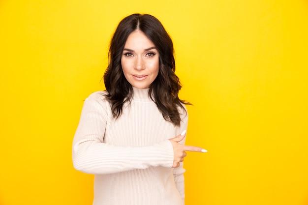 Portrait de modèle féminin pointant quelque chose d'isolé le fond jaune.