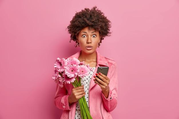 Portrait de modèle féminin surpris détient bouquet de fleurs smartphone moderne reçoit des félicitations inattendues pour son anniversaire habillé de vêtements élégants