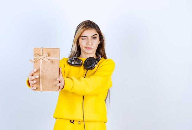 Portrait d'un modèle de fille tenant une boîte en papier avec un arc isolé sur un mur blanc