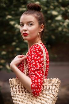 Portrait d'un modèle grand dans une robe rouge et avec un sac de paille en été dans le parc après la pluie