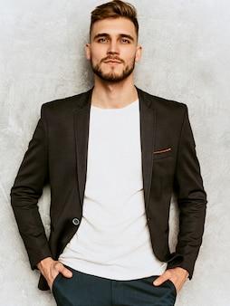 Portrait de modèle d'homme d'affaires beau hipster sérieux portant un costume noir décontracté.