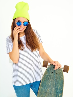 Portrait de modèle jeune femme élégante dans des vêtements d'été décontractés en bonnet jaune posant avec bureau longboard. isolé sur blanc