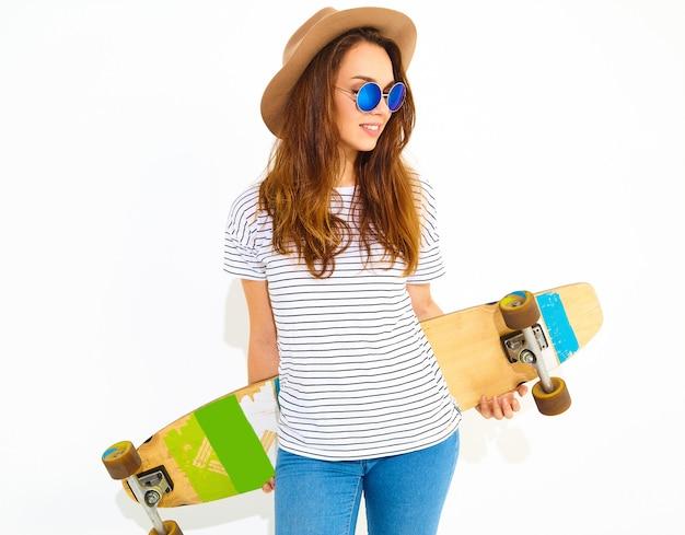Portrait de modèle jeune femme élégante dans des vêtements d'été décontractés en chapeau brun posant avec bureau longboard. isolé sur blanc