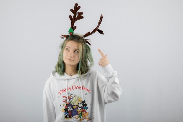 Portrait d'un modèle de jeune femme pointant sur le masque de cornes de cerf.