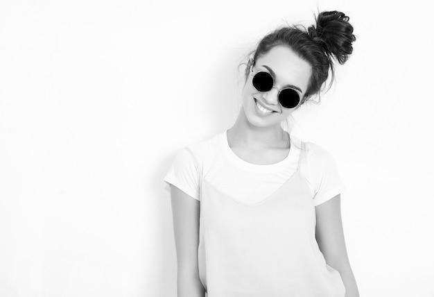 Portrait de modèle de jeune fille belle jeune femme brune avec du maquillage nude dans des vêtements colorés hipster rose d'été en lunettes de soleil posant près du mur. regardant joyeusement