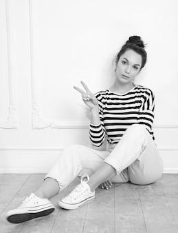 Portrait de modèle de jeune fille belle jeune femme brune avec du maquillage nude dans des vêtements d'été hipster posant près du mur. assis sur le sol et montrant le signe de la paix