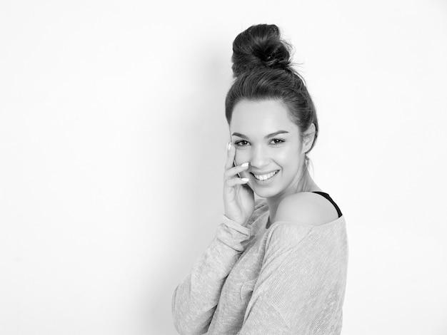Portrait de modèle de jeune fille belle jeune femme brune avec du maquillage nude dans des vêtements d'été hipster posant près du mur.