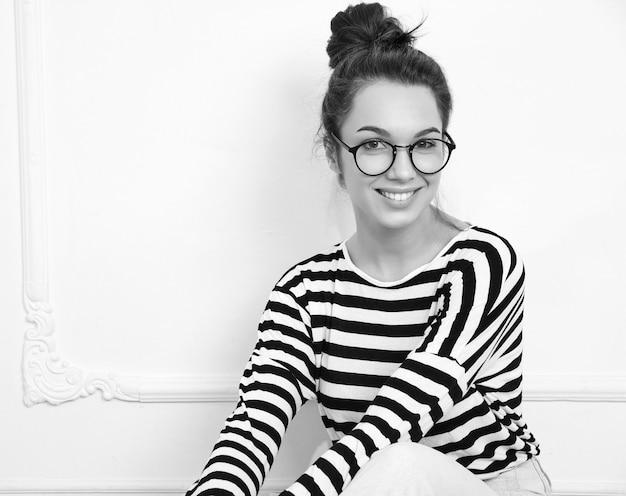 Portrait de modèle de jeune fille belle jeune femme brune avec du maquillage nue dans des verres dans des vêtements d'été hipster posant près du mur. assis par terre