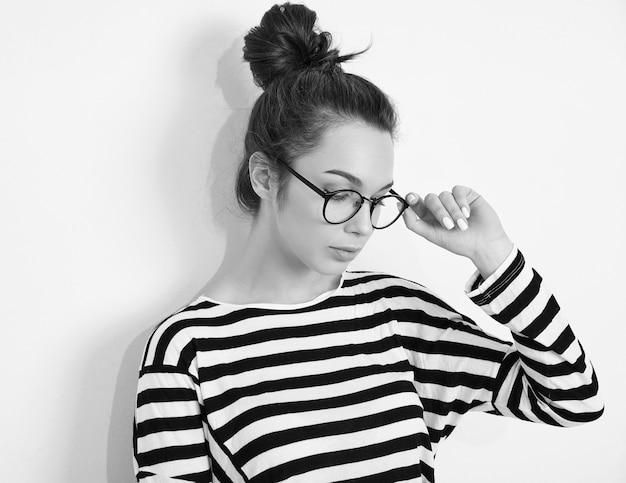 Portrait de modèle de jeune fille belle jeune femme brune avec du maquillage nue dans des verres dans des vêtements d'été hipster posant près du mur.