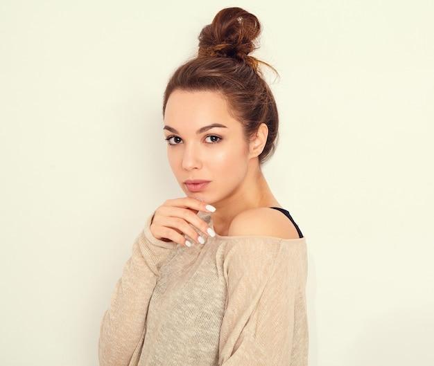 Portrait de modèle de jeune fille belle jeune femme brune avec du maquillage nue dans des vêtements d'été posant près du mur.
