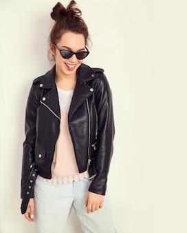 Portrait de modèle de jeune fille belle jeune femme brune avec maquillage nude portant des vêtements de veste en cuir de motard hipster d'été à lunettes de soleil posant près du mur montrant sa langue