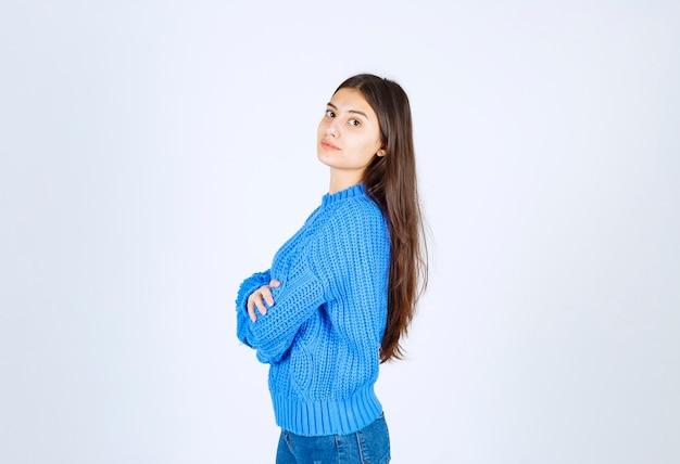 Portrait d'un modèle de jeune fille debout avec les mains croisées et avec impatience.