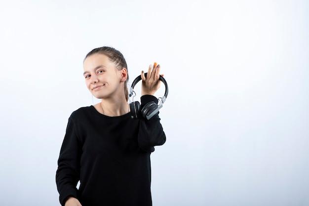 Portrait d'un modèle de jeune fille souriante tenant un casque à la main