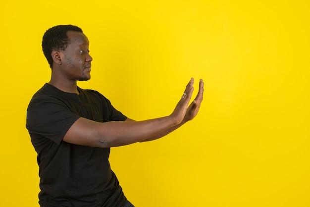 Portrait d'un modèle de jeune homme debout et poussant quelque chose devant lui