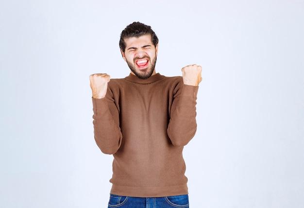 Portrait d'un modèle de jeune homme heureux dans une pose réussie.