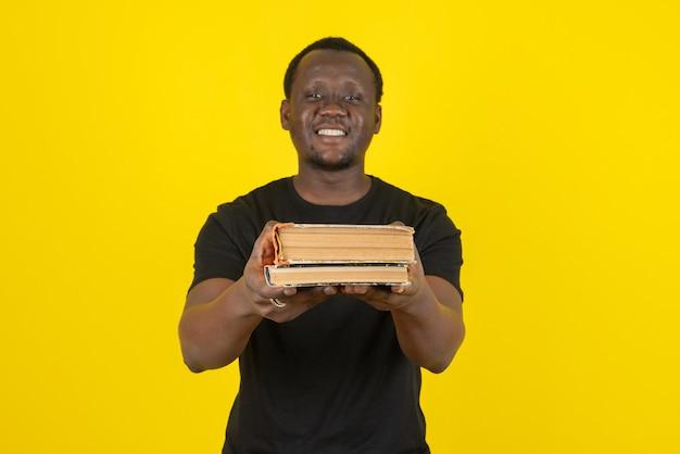 Portrait d'un modèle de jeune homme montrant des livres à la caméra contre un mur jaune